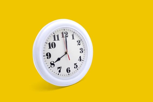 Horloge murale moderne blanche isolée sur fond jaune.