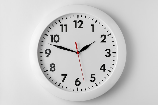 Horloge murale ronde blanche isolée sur fond gris clair, ombre naturelle
