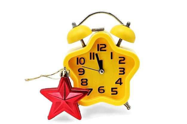 Une horloge de noël avec astérisque indique le temps restant jusqu'à minuit avec un astérisque rouge, sur fond blanc. jaune 12, 12 heures