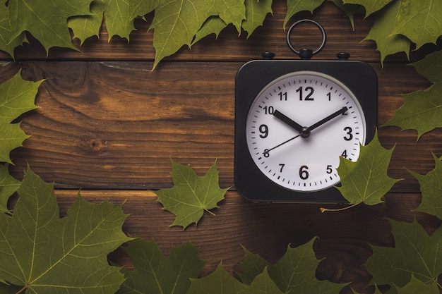 Horloge noir et blanc dans un cadre de feuilles d'érable sur fond deervyannom.
