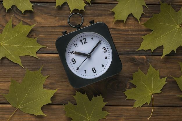 Horloge noir et blanc avec des mains et des feuilles d'érable sur un fond en bois.