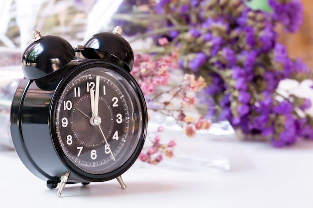 Horloge noire vintage sur table blanche avec des fleurs en violet sur fond