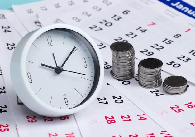 Horloge avec une pile de pièces sur un calendrier mensuel. le temps, c'est de l'argent. il est temps d'investir