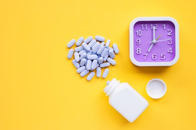 Horloge avec des pilules bleues médicales sur jaune.