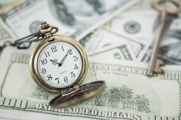 Horloge de poche sur des billets de cent dollars