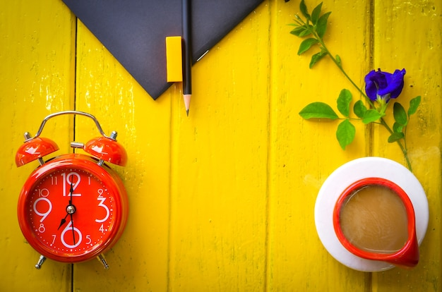 Horloge rétro avec une tasse de café et de la papeterie sur fond jaune, espace vide.