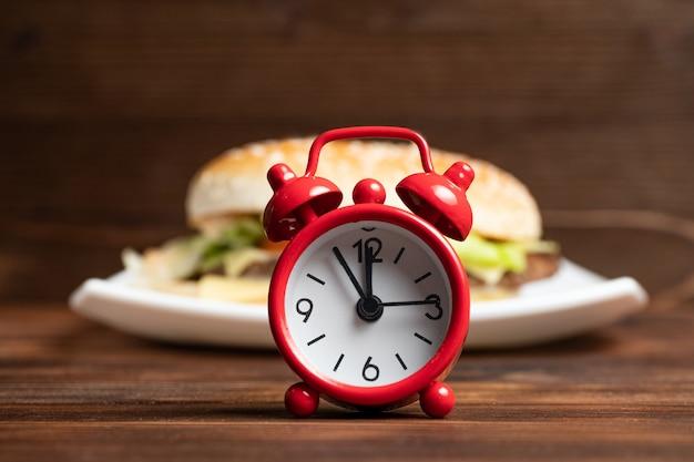 Horloge rouge et burger sur une plaque blanche et fond en bois.