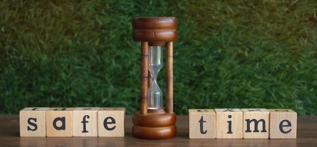 Horloge de sable mis au milieu de temps sûr mot écrit sur bois