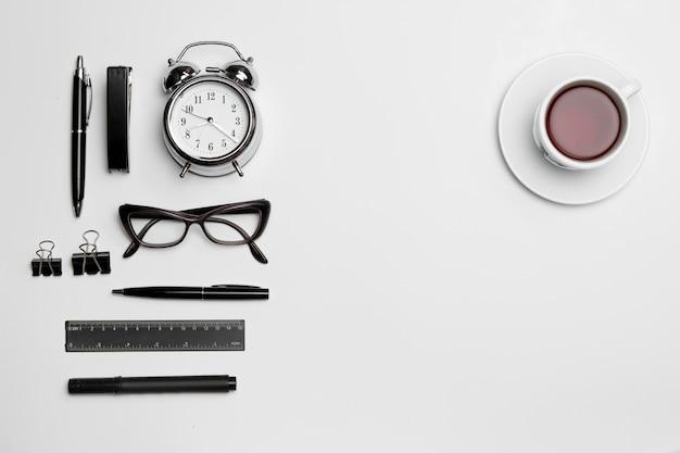 L'horloge, le stylo et les lunettes sur blanc