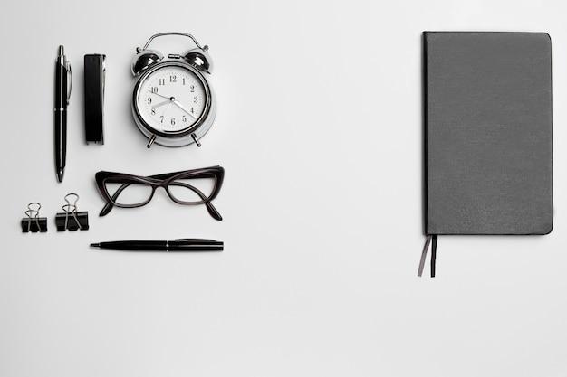 L'horloge, le stylo et les lunettes sur l'espace blanc
