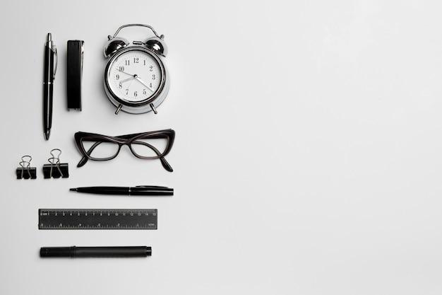 L'horloge, le stylo et les lunettes sur une surface blanche