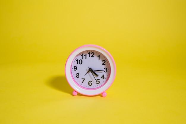 Horloge de table sur fond jaune avec espace pour le texte