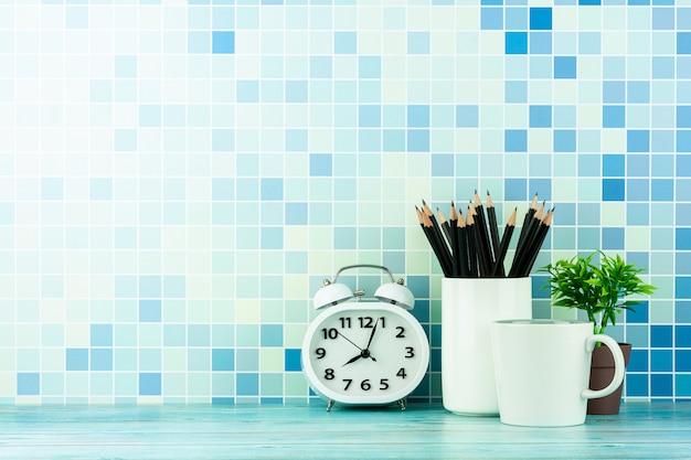 Horloge, tasse à café et un crayon sur un bureau en bois bleu