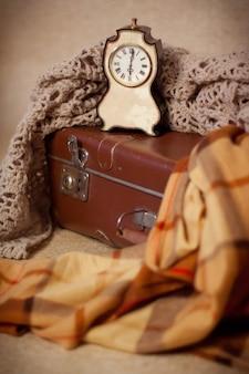 Horloge sur une valise recouverte d'une couverture tricotée et d'un plaid