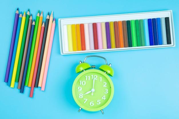Horloge verte crayon sur fond bleu style pastel