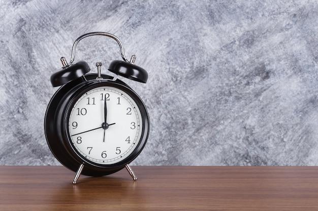 Horloge vintage de 12 heures sur fond de table et mur en bois