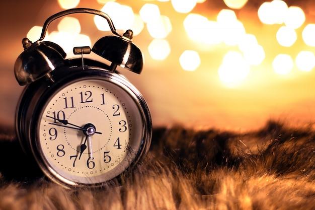 Horloge vintage sur la fourrure moelleuse dans une chambre avec belle lumière bokeh