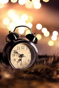 Horloge vintage sur la fourrure moelleuse dans une chambre à coucher avec belle lumière bokeh à la verticale