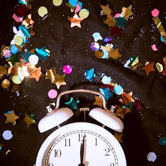 Horloge vue de dessus entourée de confettis colorés