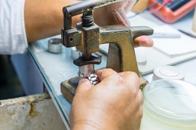 Horloger senior en train de réparer une vieille montre de poche