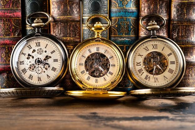 Horloges anciennes sur fond de livres vintage.