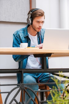 Hors du monde avec ma musique et mon ordinateur portable. jeune homme concentré dans des écouteurs travaillant sur un ordinateur portable