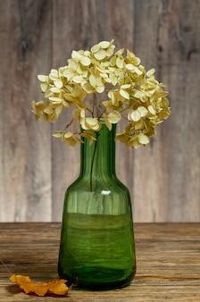 Hortensia fleur séchée se dresse dans un vase en verre vert sur une table en bois.
