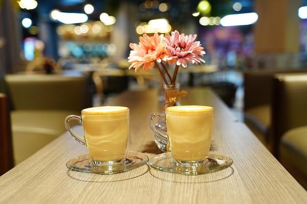 Hot art latte dans la tasse en verre sur la table en bois