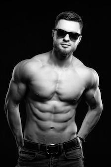 Hot bel homme fort sans chemise. fond sombre. les mains dans les poches portant des lunettes. photographie d'atelier. concept de beauté masculine. noir et blanc.