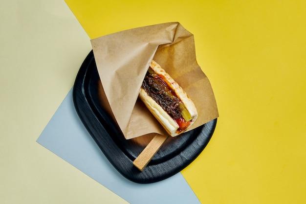 Hot-dog américain classique appétissant avec oignons caramélisés, fromage cheddar, moutarde et ketchup avec un plat de pommes de terre sur une surface colorée restauration rapide