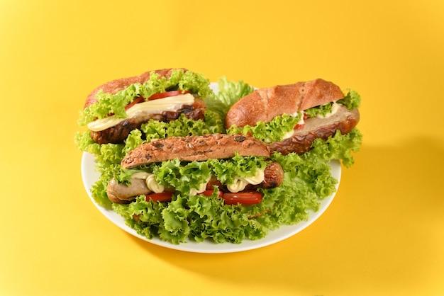 Hot dog avec beaucoup de salade verte et saucisses frites