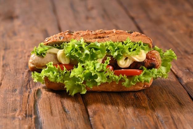 Hot-dog avec beaucoup de salade verte et vue de dessus de saucisses frites