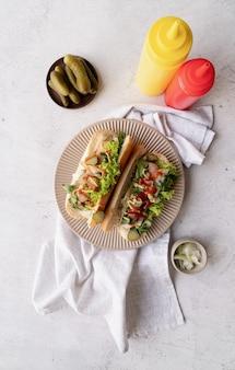 Hot-dog avec concombre de laitue saucisse et oignon sur plaque beige sur fond de béton