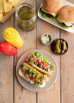 Hot-dog avec concombre de laitue saucisse et oignon sur plaque beigw sur fond de bois