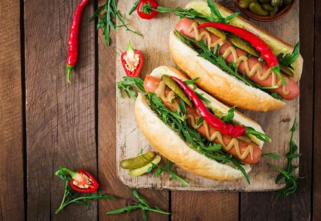 Hot-dog avec cornichons, câpres et roquette sur bois. vue de dessus