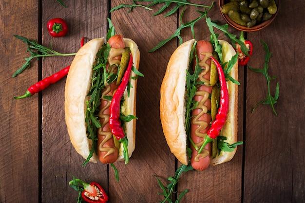 Hot-dog avec cornichons, câpres et roquette sur table en bois.