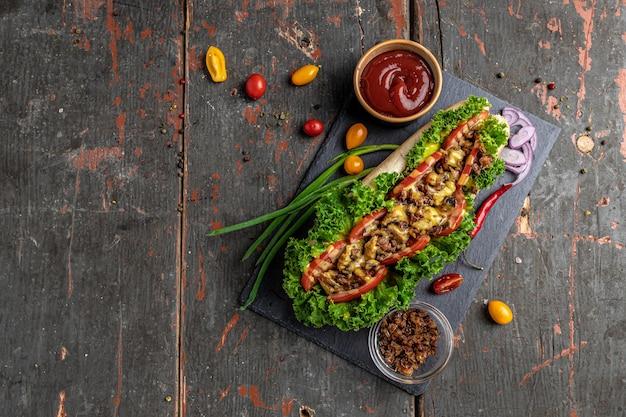 Hot-dog frais et délicieux aux oignons. viande frite, tomates, laitue et sauce au fromage. bannière, menu, lieu de recette pour le texte, vue de dessus
