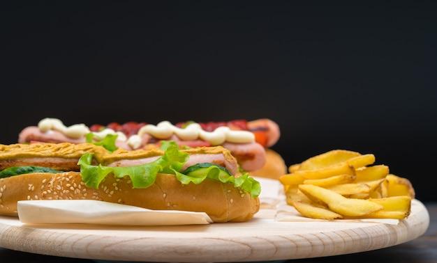 Hot-dog garni de moutarde épicée et servi avec des feux français croustillants sur une planche rustique en bois sur un fond sombre avec copie espace