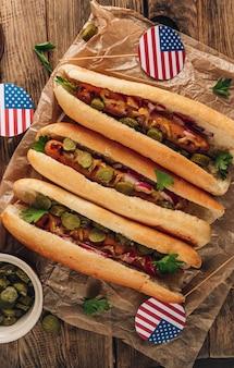 Hot-dog grillé au barbecue avec concombre mariné, oignon rouge et moutarde sur fond de bois rustique. vue de dessus