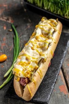 Hot-dog grillé fait maison avec des saucisses enveloppées de fromage et de maïs, gros aliments malsains