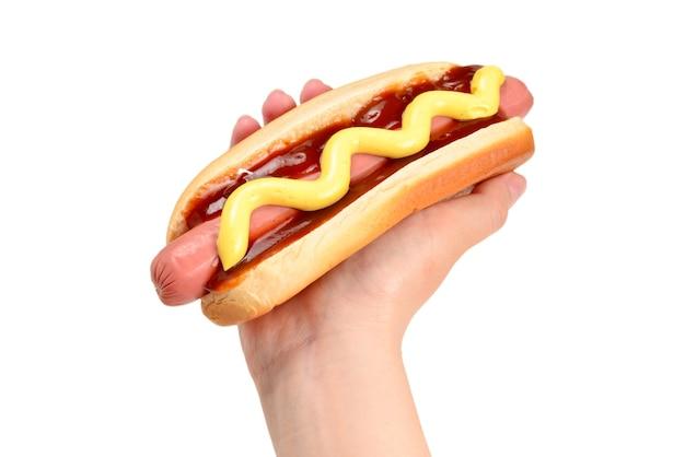 Hot-dog en main de femme isolé sur une surface blanche