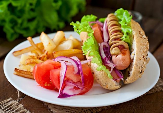 Hot-dog avec moutarde ketchup et laitue sur table en bois.