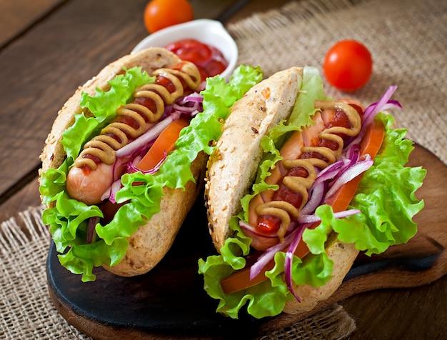 Hot-dog avec de la moutarde ketchup et de la laitue sur table en bois