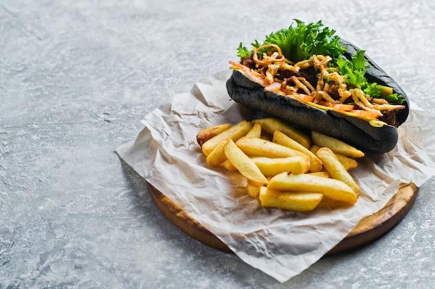 Hot dog noir avec brochette de boeuf et oignons caramélisés.