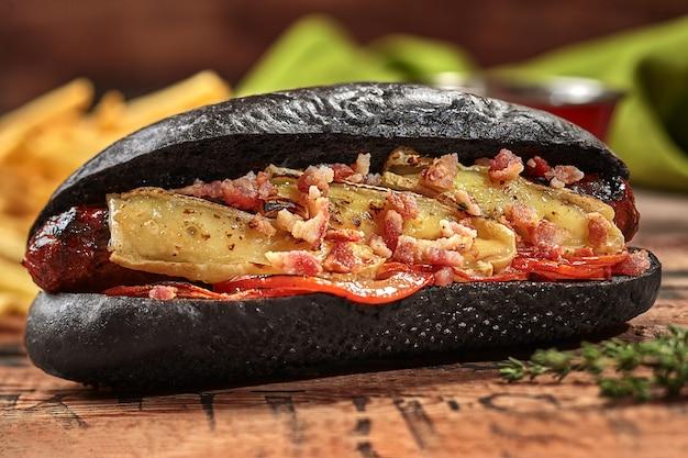 Hot-dog noir avec tomate de fromage de saucisse grillée et bacon frit