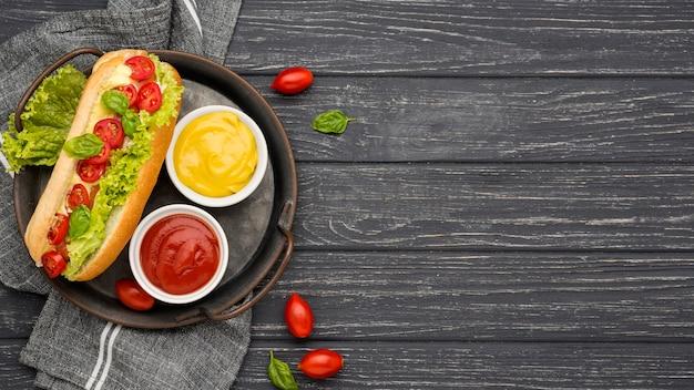 Hot-dog plat avec des bols de sauce