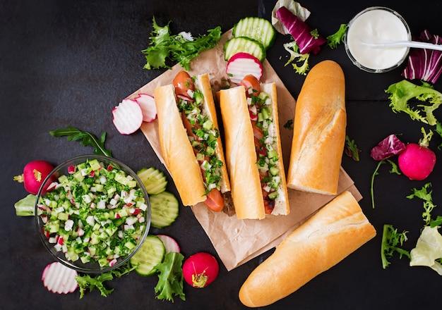 Hot dog sain habillé de yaourt et de salsa de concombre avec des radis sur fond sombre.