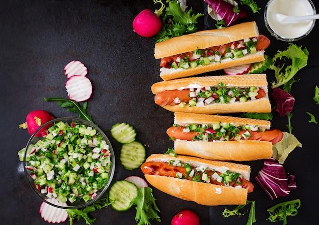 Hot dog sain habillé de yaourt et de salsa de concombre avec des radis à la noirceur.