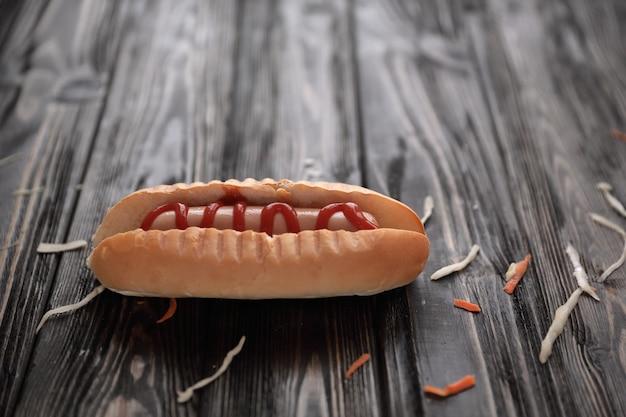Hot-dog avec sauce sur fond de bois