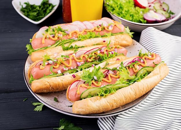 Hot-dog avec saucisse, concombre, radis et laitue sur table en bois foncé. hot-dog d'été.